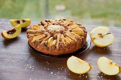 Πίτα της Apple με το κυδώνι, τους σπόρους παπαρουνών, τις σταφίδες και το σουσάμι στο σκοτεινό πιάτο που διακοσμείται με τα τεμαχ Στοκ Εικόνες