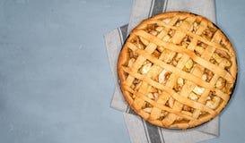 Πίτα της Apple ξινή με τις σταφίδες, τα καρύδια και την κανέλα στην εκλεκτής ποιότητας σύσταση υποβάθρου Παραδοσιακό επιδόρπιο γι Στοκ Φωτογραφία