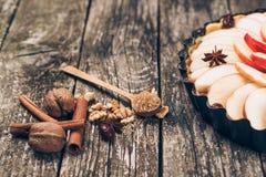 Πίτα της Apple ξινή στο αγροτικό ξύλινο υπόβαθρο Συστατικά - μήλα και κανέλα Στοκ Εικόνες