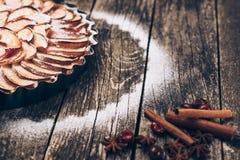 Πίτα της Apple ξινή στο αγροτικό ξύλινο υπόβαθρο Συστατικά - μήλα και κανέλα Στοκ Εικόνα