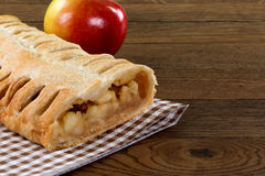 Πίτα της Apple που διακοσμείται με ένα φρέσκο μήλο σε έναν ξύλινο πίνακα με ομο Στοκ φωτογραφίες με δικαίωμα ελεύθερης χρήσης