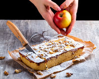 Πίτα της Apple, που ξεσκονίζεται με την κονιοποιημένες ζάχαρη και την περικοπή με ένα μαχαίρι Χέρι Στοκ Εικόνα