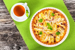Πίτα της Apple που ψεκάζεται με τη ζάχαρη τήξης που διακοσμείται με τα φύλλα μεντών Στοκ Εικόνες