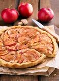 Πίτα της Apple στην περγαμηνή στον αγροτικό πίνακα Στοκ Φωτογραφία