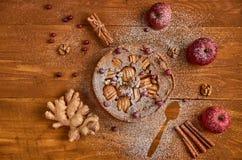 Πίτα της Apple τα φρέσκα τα βακκίνια και τα ξύλα καρυδιάς που διακοσμούνται με με τα μήλα, την πιπερόριζα και την κανέλα Κονιοποι Στοκ εικόνες με δικαίωμα ελεύθερης χρήσης
