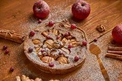 Πίτα της Apple τα φρέσκα τα βακκίνια και τα ξύλα καρυδιάς που διακοσμούνται με με τα μήλα, την πιπερόριζα και την κανέλα Κονιοποι Στοκ Φωτογραφίες