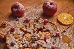 Πίτα της Apple τα φρέσκα τα βακκίνια και τα ξύλα καρυδιάς που διακοσμούνται με με τα μήλα, την πιπερόριζα, το ξηρές πορτοκάλι και Στοκ Εικόνες