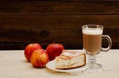 Πίτα της Apple, cappuccino και ώριμα μήλα σε ένα ξύλινο υπόβαθρο Στοκ φωτογραφία με δικαίωμα ελεύθερης χρήσης