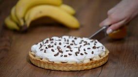 Πίτα Banoffee με τις μπανάνες, κτυπημένη κρέμα, σοκολάτα Τέμνουσα πίτα banoffee κομματιού απόθεμα βίντεο