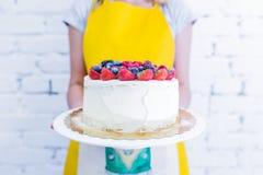 Πίτα Whoopie στο πιάτο με τα φρέσκα μούρα, κράτημα χεριών γυναικών ` s Στοκ εικόνες με δικαίωμα ελεύθερης χρήσης