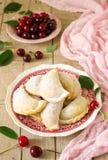 Πίτες με τα κεράσια, που ψεκάζονται με την κονιοποιημένα ζάχαρη και τα μούρα των φρέσκων κερασιών σε μια ξύλινη επιφάνεια στοκ φωτογραφίες