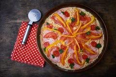 Πίτσα και διαφορετικά συστατικά σε το Σκοτεινή ανασκόπηση επάνω από την όψη στοκ φωτογραφία