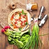 Πίτσα, καρύκευμα και πράσινα στο ξύλο Στοκ φωτογραφία με δικαίωμα ελεύθερης χρήσης