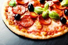 Πίτσα κρέατος με το ζαμπόν, Pepperoni και το μπέϊκον σε ένα μαύρο υπόβαθρο Στοκ εικόνες με δικαίωμα ελεύθερης χρήσης