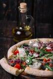 Πίτσα με μια φέτα και ένα μπουκάλι της ελιάς oul στο ξύλο backgroun Στοκ φωτογραφία με δικαίωμα ελεύθερης χρήσης