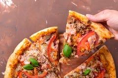 Πίτσα με τα λαχανικά και τα καρυκεύματα κρέατος σε ένα καφετί υπόβαθρο με το διάστημα αντιγράφων Τοπ όψη Στοκ Εικόνες