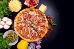 Πίτσα με τα λαχανικά και τα καρυκεύματα κρέατος σε ένα μαύρο υπόβαθρο με το διάστημα αντιγράφων Τοπ όψη Στοκ εικόνες με δικαίωμα ελεύθερης χρήσης
