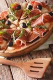 Πίτσα με τα σύκα, το prosciutto, το arugula, τις ελιές και την κινηματογράφηση σε πρώτο πλάνο τυριών Στοκ Εικόνες