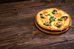 Πίτσα με την ντομάτα και μανιτάρια σε έναν καφετή ξύλινο δίσκο Στοκ εικόνες με δικαίωμα ελεύθερης χρήσης