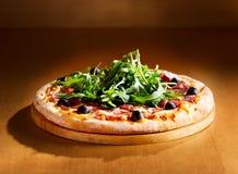 Πίτσα με τη σαλάτα ζαμπόν, σαλαμιού και arugula Στοκ Εικόνες
