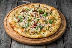 Πίτσα με τις ξηραμένες από τον ήλιο ντομάτες, το τυρί prosciutto, arugula και παρμεζάνας Στοκ Εικόνες