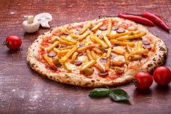 Πίτσα με τις πατάτες και τα λουκάνικα στον πίνακα στοκ εικόνες