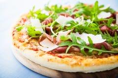 Πίτσα με το ζαμπόν της Πάρμας prosciutto, το arugula & x28 σαλάτα rocket& x29  και παρμεζάνα μπλε ξύλινο στενό σε επάνω υποβάθρου Στοκ Φωτογραφία