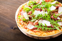 Πίτσα με το ζαμπόν της Πάρμας prosciutto, το arugula & x28 σαλάτα rocket& x29  και παρμεζάνα σκοτεινό ξύλινο στενό σε επάνω υποβά Στοκ Φωτογραφία