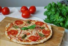 Πίτσα με το ζαμπόν, τις ντομάτες και το βασιλικό Στοκ Φωτογραφία