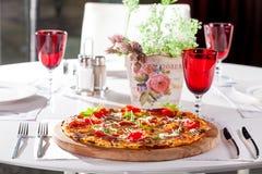 Πίτσα με το κρέας, ντομάτες, τυρί σε έναν ξύλινο πίνακα στον καφέ Στοκ Φωτογραφίες