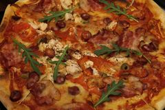 Πίτσα με το μπέϊκον, τα λουκάνικα, το ζαμπόν, την ντομάτα και τις ελιές Ψεκάστε με το arugula και εξυπηρετημένος με την ντομάτα κ Στοκ Φωτογραφίες
