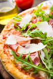 Πίτσα με το prosciutto & x28 Πάρμα ham& x29 , arugula & x28 σαλάτα rocket& x29  και παρμεζάνα σκοτεινό ξύλινο στενό σε επάνω υποβ Στοκ Εικόνα