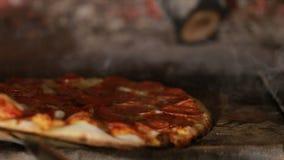 Πίτσα που περιστρέφεται και που μαγειρεύει στο φούρνο τούβλου φιλμ μικρού μήκους