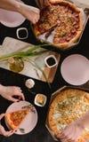Πίτσα που τίθεται στον ξύλινο πίνακα με τα φωτεινά πιάτα για το κόμμα Σκοτεινή αγροτική τονίζοντας φωτογραφία τροφίμων Τοπ εικόνα Στοκ Εικόνες