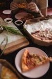 Πίτσα που τίθεται στον ξύλινο πίνακα με τα φωτεινά πιάτα για το κόμμα Σκοτεινή αγροτική τονίζοντας φωτογραφία τροφίμων Τοπ εικόνα Στοκ φωτογραφία με δικαίωμα ελεύθερης χρήσης