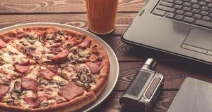 Πίτσα σε ένα πιάτο, ένα μαύρο lap-top, ένα ηλεκτρονικό τσιγάρο ή vape, ένα κινητό τηλέφωνο και ένα ποτήρι του χυμού φρούτων στον  στοκ φωτογραφία με δικαίωμα ελεύθερης χρήσης