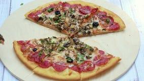 Πίτσα σε μια στρογγυλή πιατέλα r Τα χέρια μερικών ανθρώπων παίρνουν τα κομμάτια της πίτσας φιλμ μικρού μήκους
