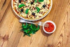 Πίτσα σπιτική με τη σάλτσα στο ξύλινο υπόβαθρο Στοκ Φωτογραφίες