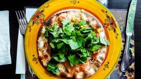 Πίτσα το σολομό και τα πράσινα που εξυπηρετούνται με με το δίκρανο και μαχαίρι στο εστιατόριο Στοκ Εικόνες