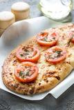 Πίτσα, ψωμί με το τυρί και κόκκινες ντομάτες, ελαιόλαδο καρυκευμάτων Στοκ φωτογραφία με δικαίωμα ελεύθερης χρήσης