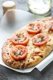 Πίτσα, ψωμί με το τυρί και κόκκινες ντομάτες, ελαιόλαδο Στοκ Φωτογραφία