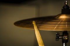 παίζει ένα ραβδί τυμπάνων στο γεια-καπέλο ή το κύμβαλο γύρου Στοκ Εικόνα