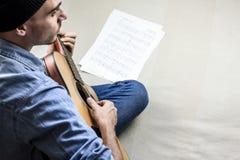 Παίζοντας ένα λαϊκό τραγούδι στην ακουστική κιθάρα στο σπίτι στοκ φωτογραφίες