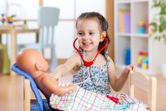 Παίζοντας γιατρός παιδιών με το παιχνίδι στο σπίτι Στοκ Φωτογραφίες