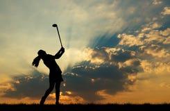 Παίζοντας γκολφ παικτών γκολφ σκιαγραφιών στο όμορφο ηλιοβασίλεμα Στοκ φωτογραφία με δικαίωμα ελεύθερης χρήσης