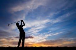Παίζοντας γκολφ παικτών γκολφ σκιαγραφιών στο όμορφο ηλιοβασίλεμα Στοκ εικόνες με δικαίωμα ελεύθερης χρήσης