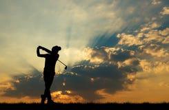Παίζοντας γκολφ παικτών γκολφ σκιαγραφιών στο όμορφο ηλιοβασίλεμα Στοκ Εικόνες