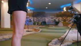 Παίζοντας μίνι γκολφ Μια νέα γυναίκα που παίζει το μίνι γκολφ στο εσωτερικό Χτύπημα της σφαίρας απόθεμα βίντεο