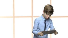 Παίζοντας παιχνίδια ικανοποιημένων παιδάκι στον υπολογιστή ταμπλετών απόθεμα βίντεο