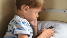 Παίζοντας παιχνίδια κινητών τηλεφώνων αγοριών στο τραίνο απόθεμα βίντεο